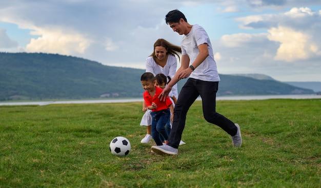 Asiatische familie. vater mutter und tochter sohn laufen und fußball spielen auf dem rasen