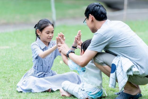 Asiatische familie zeit im urlaub verbringen durch gemeinsame aktivitäten beim spielen in einem grünen garten