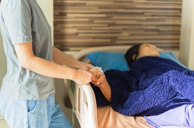 Asiatische familien besuchen die geduldige hand einer älteren frau, die hand auf der krankenstation hält
