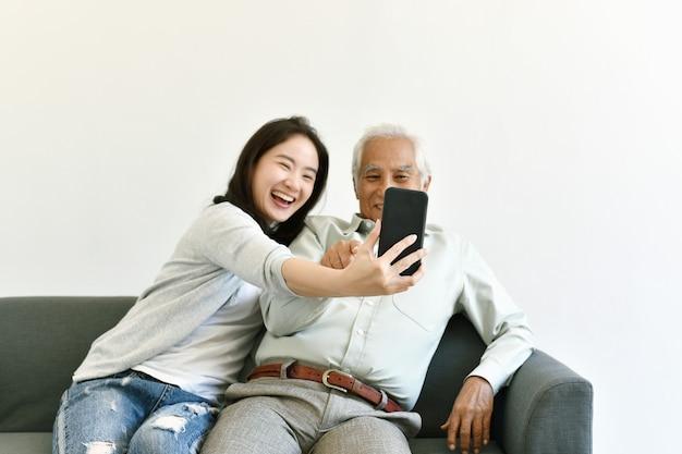 Asiatische familienbeziehung, tochter und älterer vater nutzen gemeinsam das smartphone für selfies. senioren lernen, wie man soziale medien und digitale technologieplattformen nutzt.