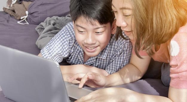 Asiatische familienmutter und -sohn, die auf laptop-computer aufpasst.