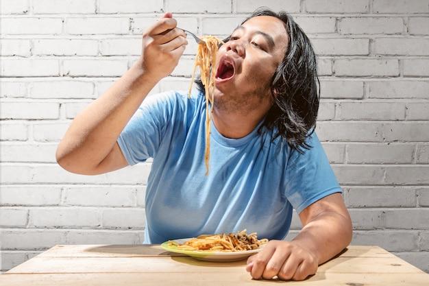 Asiatische fette mannmahlzeit die schnellimbissspaghettis