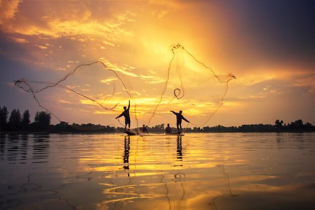 Asiatische fischer auf bootsfischen am see, thailand-landschaft