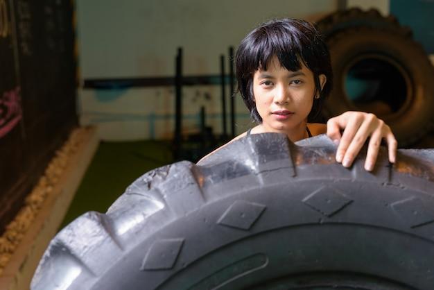 Asiatische fitnessfrau, die rad-lkw-reifen im fitnessstudio drückt und dreht