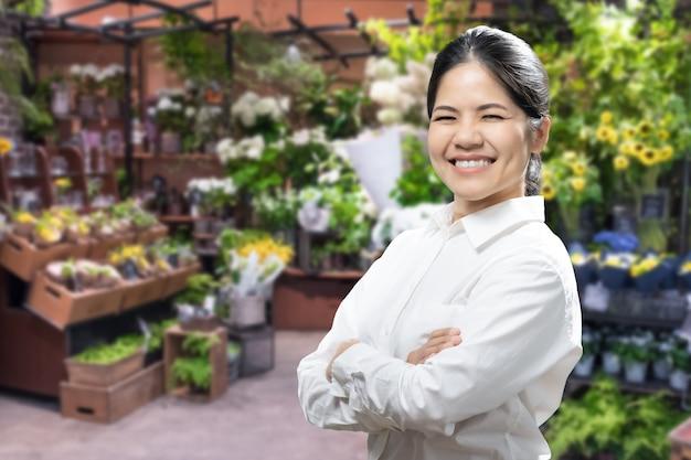 Asiatische floristin oder geschäftsinhaberin mit blumenladenhintergrund