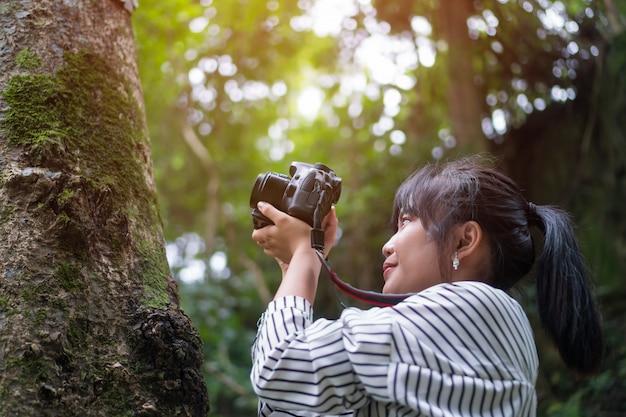 Asiatische fotograffotoaufnahme-arbeitskamera. frau, die foto mit dem lächeln für hobby macht