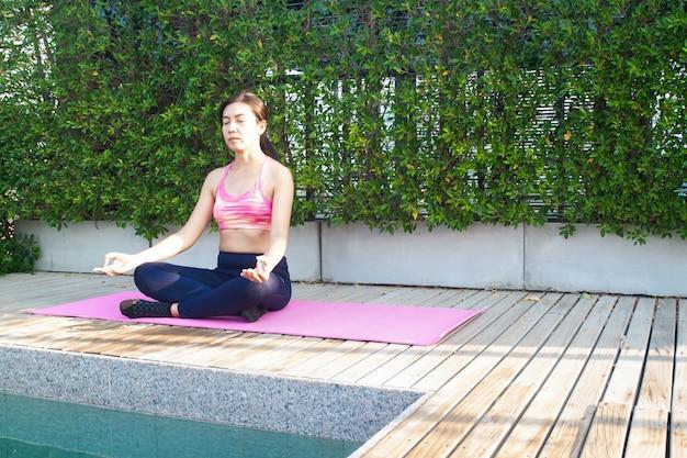 Asiatische frau 40s, die meditation nahe swimmingpool tut. gesundheit der frau