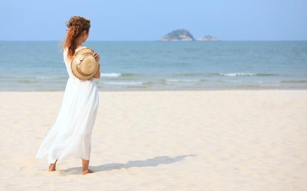 Asiatische frau am strand mit blick auf das meer