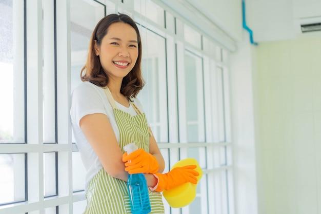 Asiatische frau arm gekreuzt, während auf spiegel mit ausrüstung für die reinigung des hauses gelehnt