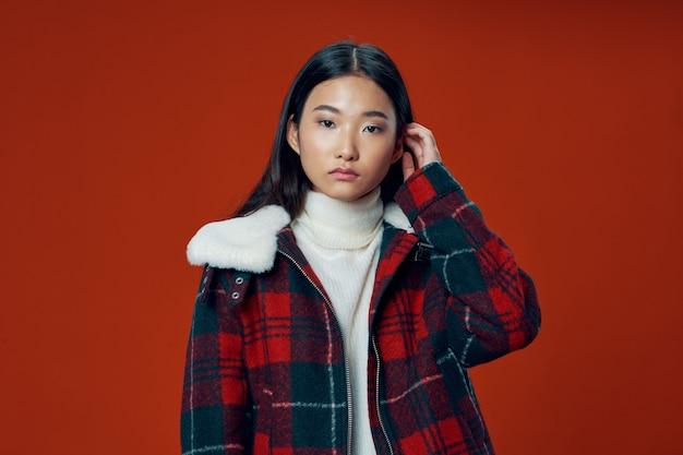 Asiatische frau auf hellem farbhintergrund, der modell aufwirft