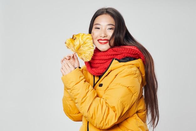 Asiatische frau auf hellem farbraum, der modell aufwirft