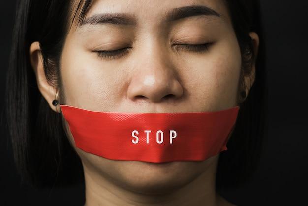Asiatische frau augenbinde, die mund mit rotem klebeband einwickelt