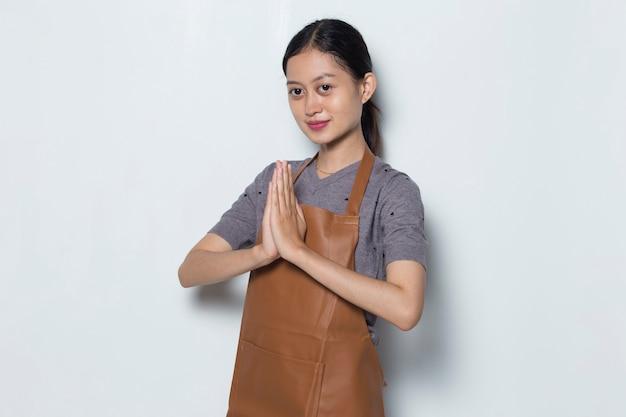 Asiatische frau barista tragen schürze willkommensgeste café servicekonzept
