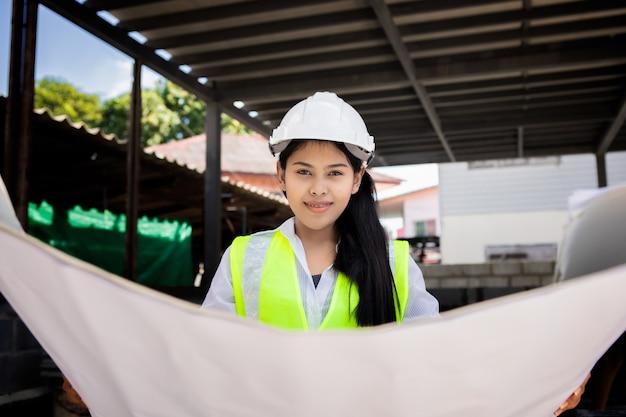 Asiatische frau bauingenieur papierplan gebäude architekt tragen weißen sicherheitshelm blick auf baustelle.