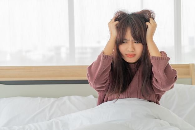 Asiatische frau belasten und ernst auf dem bett