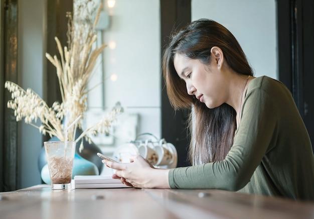 Asiatische frau benutzen einen smartphone und trinken gefrorene schokolade am hölzernen schalter in der kaffeestube