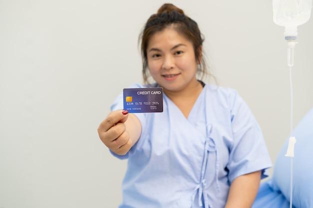 Asiatische frau bleibt im krankenhaus und zeigt eine kreditkarte mit dem daumen nach oben