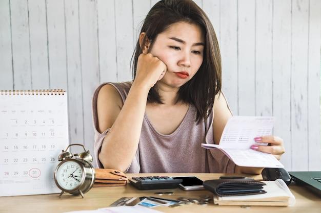 Asiatische frau der arbeitslosigkeit, die sparkonto betrachtet