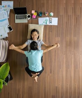 Asiatische frau der draufsicht mit kindern, die am haus auf holzboden spielen