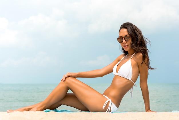 Asiatische frau der jungen sonnenbräunehaut im weißen biniki badeanzug am strand