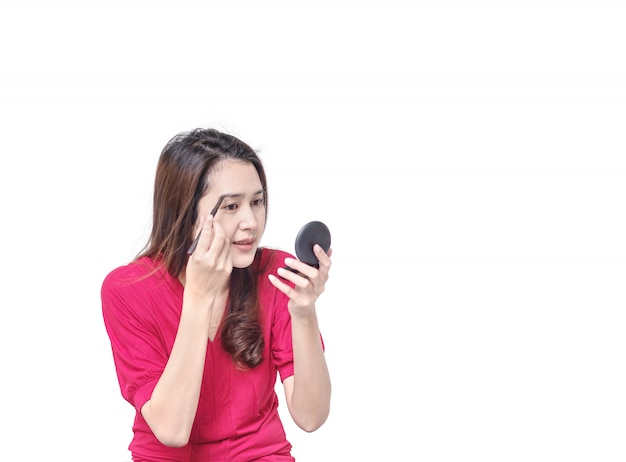Asiatische frau der nahaufnahme bilden augenbraue mit dem augenbrauenstift, der auf weißem hintergrund im kosmetischen konzept lokalisiert wird