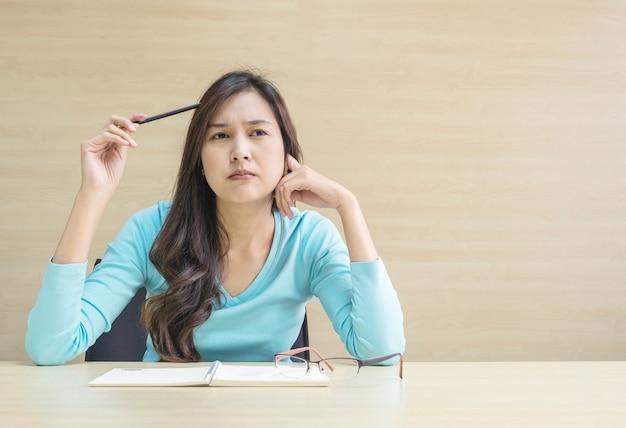 Asiatische frau der nahaufnahme, die mit denkendem gesicht und einem bleistift in ihrer hand auf unscharfem hölzernem schreibtisch arbeitet