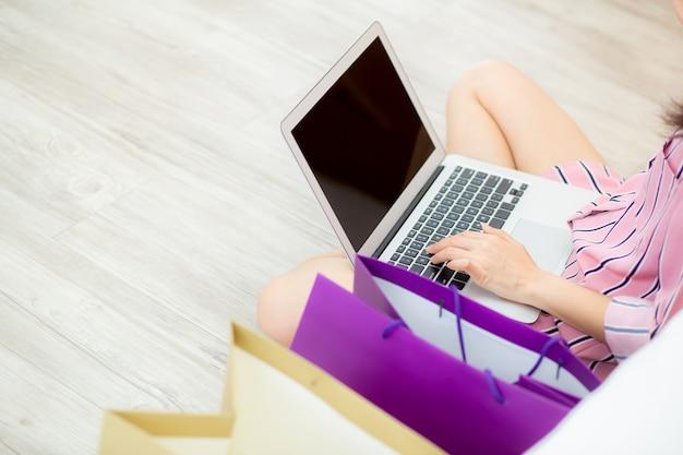 Asiatische frau der nahaufnahme, die online mit laptop kauft