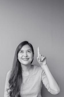 Asiatische frau der nahaufnahme hält einen fingerpunkt zum raum mit lächelngesicht auf strukturiertem hintergrund der unscharfen zementwand