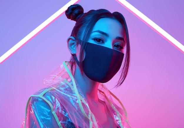 Asiatische frau der virenmaske, die gesichtsschutz um buntes neon trägt