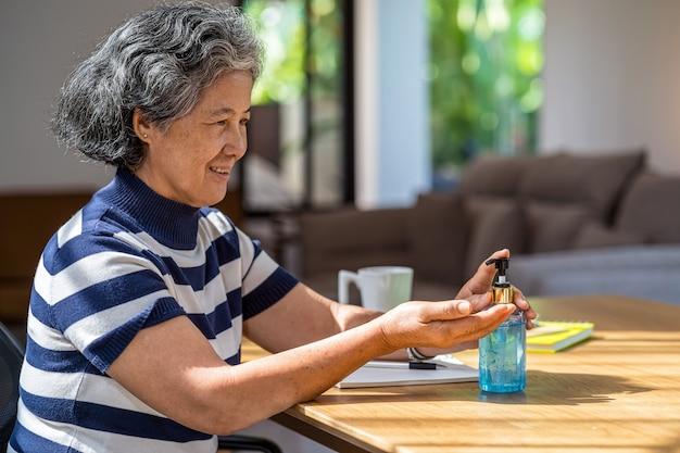 Asiatische frau des alten mannes, die händedesinfektionsmittel durch pumpen von alkoholgel und waschen vor der arbeit verwendet