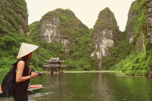 Asiatische frau des fotografen, die slr-kameraberufsphotographie in ninh binh, vietnam hält