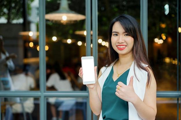 Asiatische frau des geschäfts, die smartphone mit modell oben lächelt und zeigt