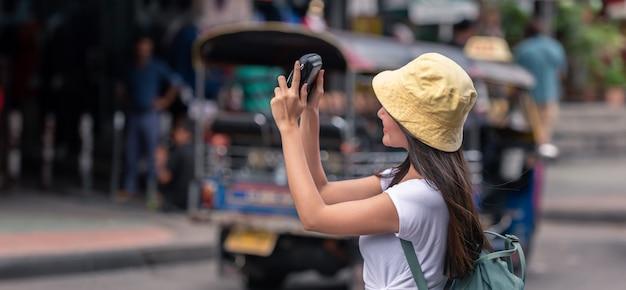 Asiatische frau des glücklichen reisenden auf straßenmarkt mit kamera, in bangkok-stadt von thailand.