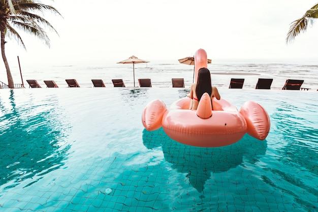 Asiatische frau des glücklichen reisenden mit bikini entspannen sich auf großem rosa flamingopool, der im schwimmbad bei thailand, sommerreiseferienkonzept schwimmt