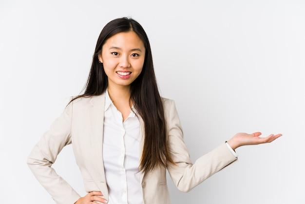 Asiatische frau des jungen geschäfts, die etwas auf einer palme zeigt und eine andere hand auf taille hält