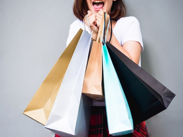 Asiatische frau des jungen glücklichen sommers kaufend mit einkaufstaschen auf grauem hintergrund am kopienraum