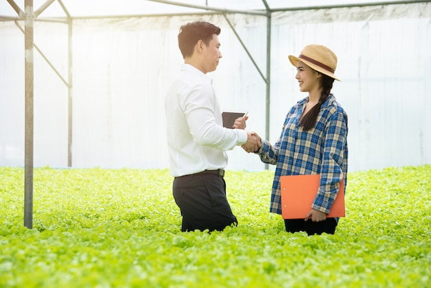 Asiatische frau des jungen landwirts, die hand mit geschäftsmann im organischen gewächshausgemüsebauernhof der hydrokultur rüttelt.