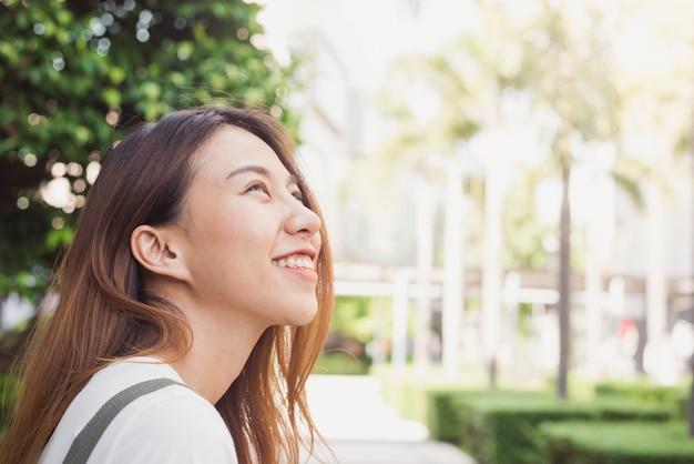 Asiatische frau des jungen reisenden, die schöne sonnige schmale straßen in bangkok bewundert