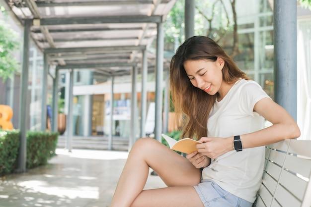 Asiatische frau des jungen reisenden, die schöne sonnige schmale straßen in bangkok, thailand bewundert