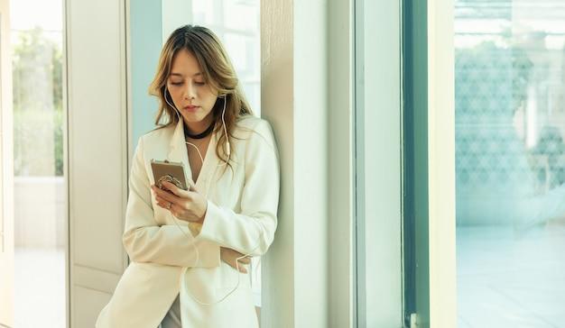 Asiatische frau des jungen schönheitsgeschäfts stehen nahe fenster und verwendet digitales smartphone. mädchen, das mobilen computer hält und seinen bildschirm betrachtet. frau mit gadget. internet der dinge