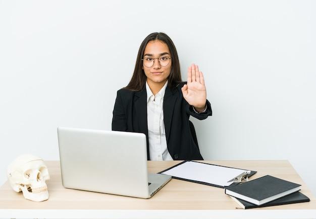 Asiatische frau des jungen traumatologen lokalisiert auf weißer wand, die mit ausgestreckter hand steht, die stoppschild zeigt, das sie verhindert