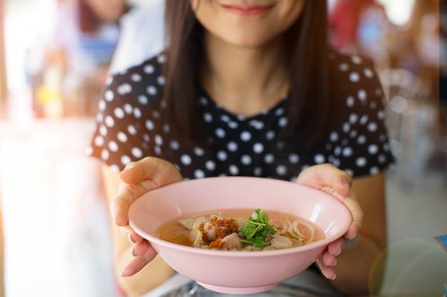 Asiatische frau des lächelns, die eine schüssel der nudel im restaurant hält