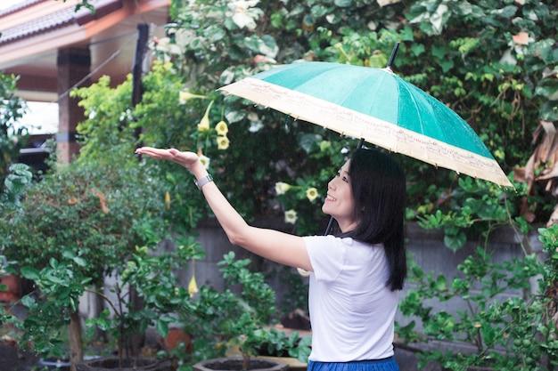 Asiatische frau des lächelns hat spaß in den regentropfen mit dem halten des regenschirmes