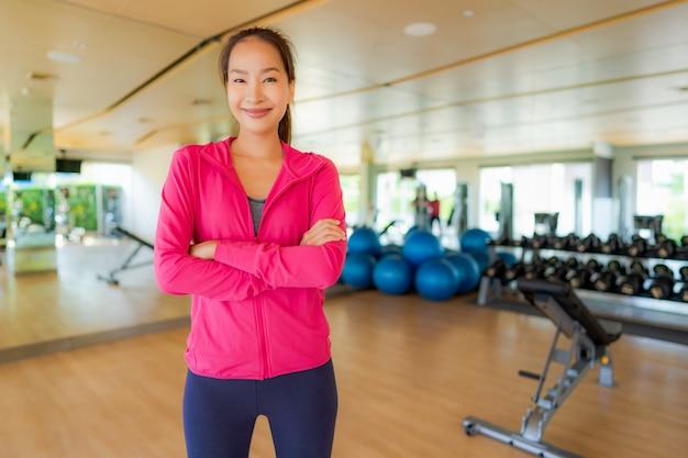 Asiatische frau des porträts, die trainiert und in der turnhalle ausarbeitet