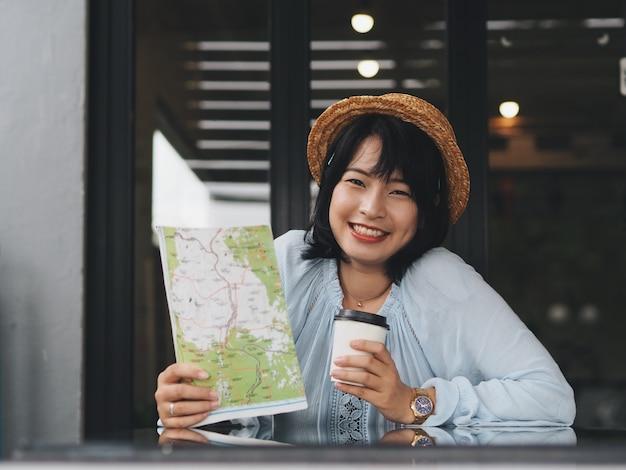 Asiatische frau des reisenden, die in der kaffeestube sich entspannt.