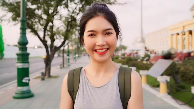 Asiatische frau des reisenden, die zur kameraurlaubsreise in bangkok, thailand glücklich lächelnd sich fühlt