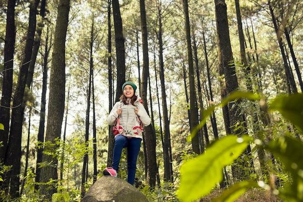 Asiatische frau des reisenden mit rucksack erforschen grünen wald