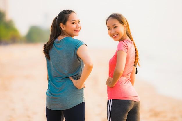 Asiatische frau des schönen jungen sports des porträts, die auf dem strand nahe meer und ozean zur sonnenaufgang- oder sonnenuntergangzeit läuft und trainiert