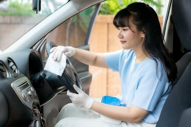 Asiatische frau desinfiziert lenkrad des autos durch desinfektionsmittel einweg-tücher aus box. verhindern sie das virus und die bakterien, verhindern sie covid19, corona-virus,