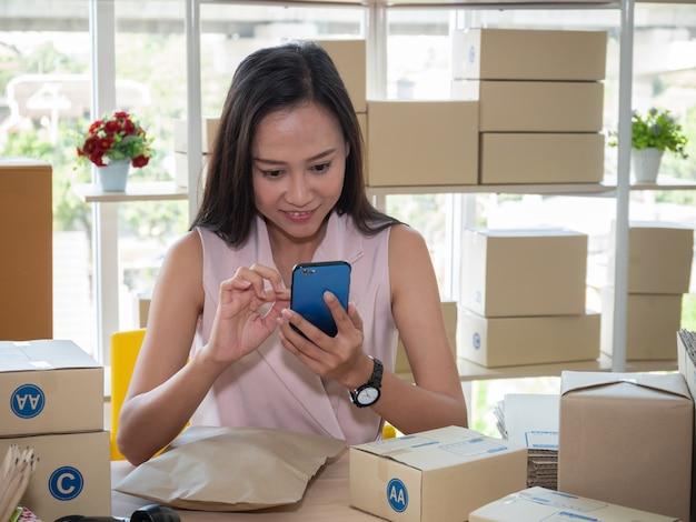 Asiatische frau, die adresse auf paketbox schreibt und produktbestellung auf smartphone überprüft